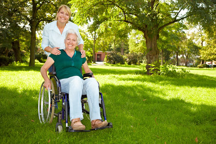 Smiling lady in wheelchair outside on the lawn with caregiver