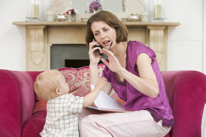 Mother on phone with toddler reaching out to her